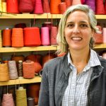 Marianne Fairbanks poses in front of a colorful wall of yarn