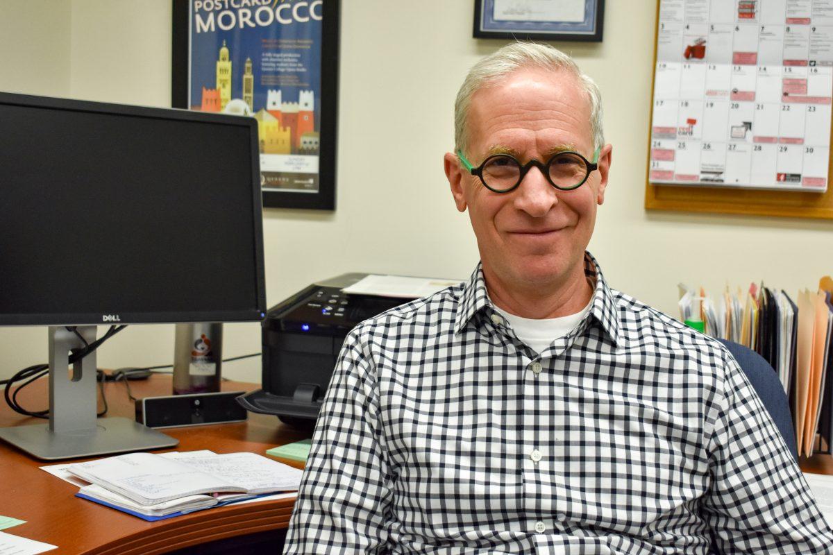 Photo of David Ronis sitting at his desk