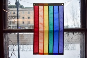 A LGBT flag hangs in front of a window in the LGBTCC