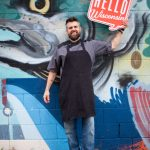 Chef, restaurant owner, and television host Luke Zahm poses behind his cafe with the Wisconsin Idea Seminar sign.