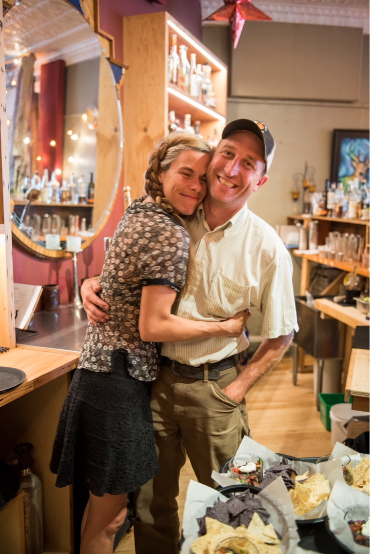 Dani Lind, owner and head chef of Rooted Spoon in Viroqua, hugs her husband Mike, who raises grass-fed beef on their 80-acre farm. (Image by Drew Shonka Photography.)