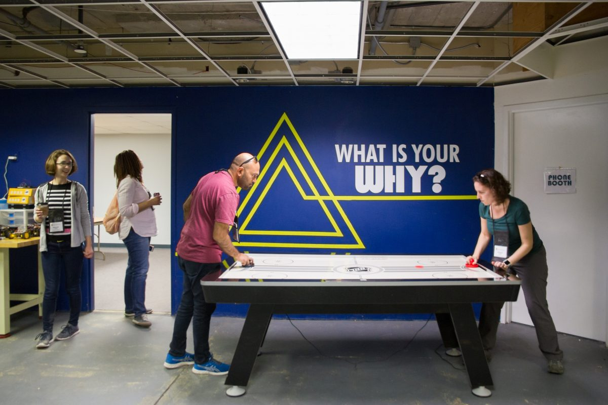 Two Wisconsin Idea Seminar participants play air hockey at the IDEA Center in Stevens Point during the 2019 River Tour.