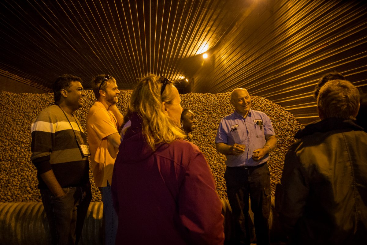 With a mountain of red seed potatoes serving as a backdrop, Steve Diercks introduces Wisconsin Idea Seminar participants to Coloma Farms. (Photo by Catherine Reiland / UW-Madison)