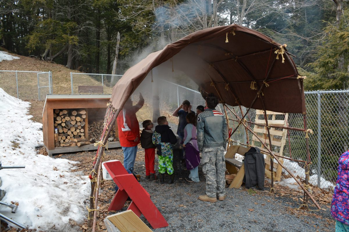 Bayfield High School students and a cultural liaison teach elementary school students about the maple sap boiling process. The traditional longhouse-style shelter was built by the high school students. (Image courtesy of Rick Erickson/Bayfield High School)